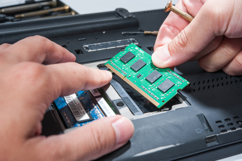 Person's hands installing RAM circuit board in a laptop