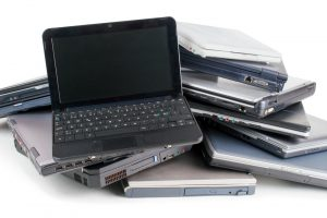 Pile of used laptops with one open showing a dark screen