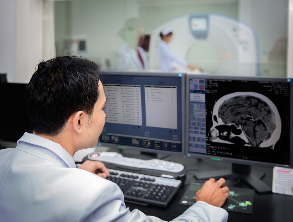 Doctor in front of a CT scan computer