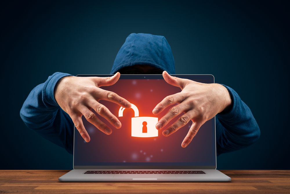 Hooded man's hands surrounding a laptop screen with broken lock icon